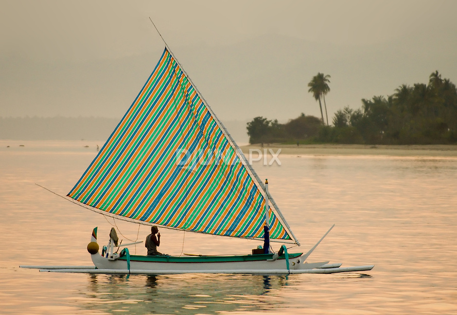 Fisherman returns home at sunrise in a traditional sailboat, Gili Air, Lombok, Indonesia