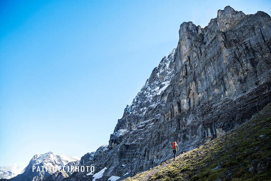 A woman hiking beneath the Eiger North Face (Norwand) on the Eiger Trail on her way to the Eiger Rotstock. Grindelwald, Switzerland.