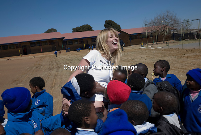 SOWETO, SOUTH AFRICA - SEPTEMBER 1: Mischa Barton, the actress and model, interacts with school children at Winnie Ngwevekazi Primary School on September 1, 2008 in Soweto, outside Johannesburg, South Africa. Mischa Barton spent 2 days visiting Save The Children supported projects in South Africa, meeting school children and young children. Save The Children are helping about 51,000 children made by HIV/AIDS and poverty to access food, healthcare, social security and education. (Photo by Per-Anders Pettersson/Getty Images For Save The Children).