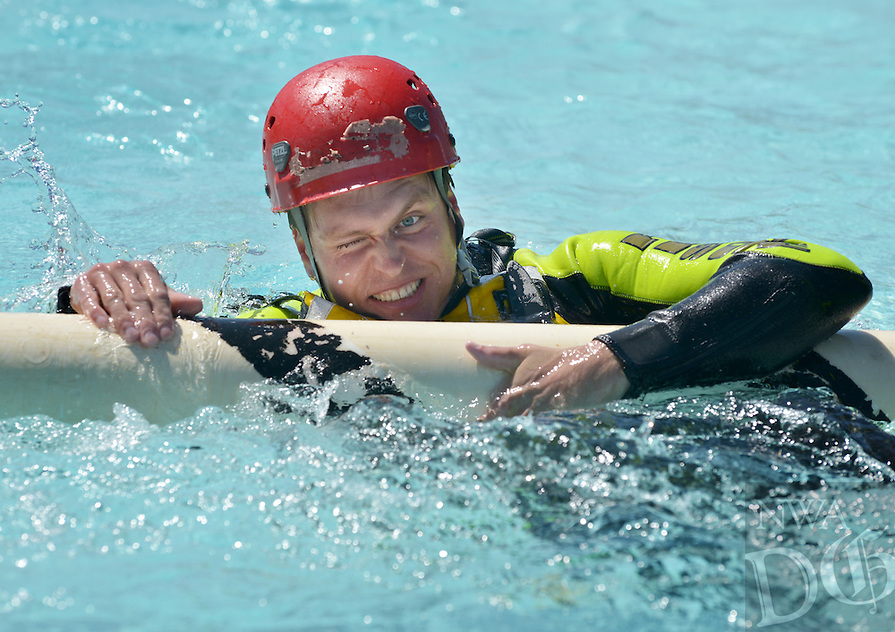 NWA Democrat-Gazette/BEN GOFF -- 05/11/15 Kyle Bishop, Rogers firefighter/EMT, fights his way over a 'strainer' during swift water rescue training at the Rogers Aquatics Center on Monday May 11, 2015. In whitewater terminology, a strainer is any large object, often a fallen tree, that allows water to flow through, but blocks larger objects, creating a potentially dangerous situation where someone can be pinned by the current. Rogers, Springdale and Bella Vista firefighters are taking part in four days of training with R.B. Ellis of Tech Resq (CQ), based in Tulsa, Okla.