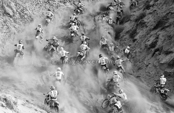 Enduro du Touquet 1992. Dirt bike beach race at Le Touquet, Normandy, France. --- No releases available, but releases may not be necessary for certain uses. Automotive trademarks are the property of the trademark holder, authorization may be needed for some uses. --- Info: A thousand motorcycles take part in this mad event. The race starts along the beach, followed by a run into the sand dunes. The entry point in the dunes is most spectacular: All motorbikes have to pass through a small opening in the dunes. Once the fast professional drivers have flown through, this first passage developes into a true bottleneck with many hundreds of motorbikers trying to get through at the same time. Motorcycles are strewn all over the place. Many have fallen, others have already broken down. In the meantime, the professional riders are progressing quickly. But their riding style changes from racing full-out as soon as they are approaching the lappers from behind. Outmaneuvering them at high speeds is an art form! After three hours it's all over.....