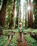 USA, California, Eureka, 103 year old woman standing in the redwood trees