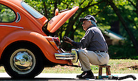 "Howard Boykin replaces an air hose on his 1971 Volkswagen Beetle Wednesday in front of his Anderson home. Mr. Boykin, who also has a Honda Civic, says he thinks of this car as a toy. ""I don't run this car much,"" he said. ""Gas is too expensive to run it everyday."""