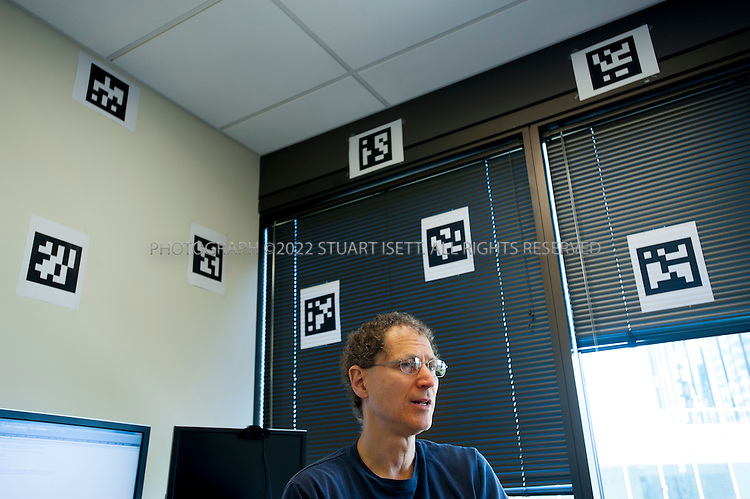 8/2/2012--Bellevue, WA, USA..Michael Abrash speaking at gaming software maker Valve. Behind him are 'fiducials', optical markers being used in the development of an artificial reality head set being made by Valve...The office is set up as a 'boss less' office that is fluid and non-hierarchical. Desks come with wheels so that they can be easily moved and reconfigured to create new work spaces for new projects. The desks can also be raised or lowered for comfort or to create a standing work space...©2012 Stuart Isett. All rights reserved.