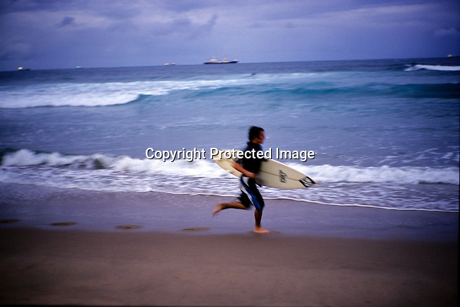 dippchi00613 Children. surfing, sport, beach, boys, white, boards, Surfers on the beach as the sun sets on the Durban beach front on July 6, 2004 in Durban, Natal , South Africa..©Per-Anders Pettersson/iAfrika Photos