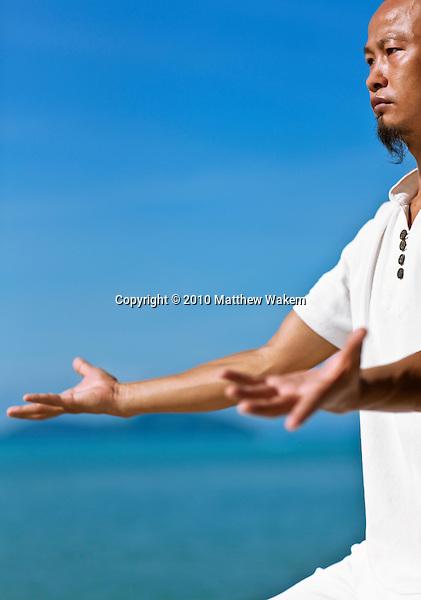 Man Practices Qi Gong at Kamalaya, Koh Samui, Thailand. Qi Gong Master Dr. Song practices morning Qi Gong by the beach at Kamalaya resort.