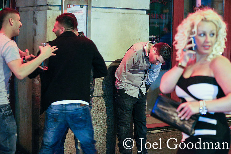 © Joel Goodman - 07973 332324 . No syndication permitted . 01/01/2014 . Manchester , UK . A man stands bent forward against a wall as others continue their evening around him . Revellers see in the New Year in Manchester today (January 1st 2014) as police report that officers are at full stretch responding to calls . Photo credit : Joel Goodman