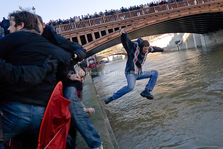 An activist falls into the river Seine while the police evacuate hundreds of tents installed by the Don Quichotte association to protest about housing policies of the government.