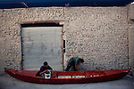 NAJAF, IRAQ: Two boat makers paint a boat in the Najaf market...Daily life continues in relative peace in the Iraqi city of Najaf...Photo by Ali Arkady/Metrography