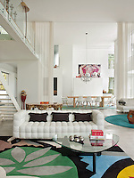 An inspiring, open plan living and dining space with a double height ceiling. A Noguchi table stands in front of a white Josef Hoffmann Kubus sofa. Vibrant carpets from Carpet Diem enliven the room.