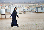 A woman walks in the Zaatari refugee camp near Mafraq, Jordan. Established in 2012 as Syrian refugees poured across the border, the camp held more than 80,000 refugees by early 2015, and was rapidly evolving into a permanent settlement. The ACT Alliance provides a variety of services to refugees living in the camp.