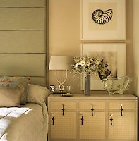 A pair of shell prints on the fabric-covered walls of the bedroom