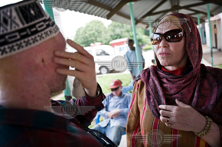 Madame Al-Shaymaa J. Kwegyir (right) visits a man with albinism at the general hospital in Dar es Salaam. The most common physical problems are skin diseases due to overexposure to the sun. Kwegyir is Tanzania's first albino Member of Parliament. The nomination of an albino MP is a first step in the fight against the widespread belief that albinism is the result of a curse. Discrimination against albinos is a serious problem throughout sub-Saharan Africa, but recently in Tanzania albinos have been killed and mutilated, victims of a growing criminal trade in albino body parts fuelled by superstition and greed. Limbs, skin, hair, genitals and blood are believed by witch doctors to bring good luck, and are sold to clients for large sums of money, carrying with them the promise of instant wealth.