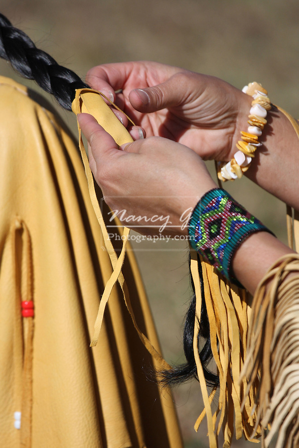 Two Native American Indian women with fringe leather dress braiding eachother braids Focus on the leather band on the hair