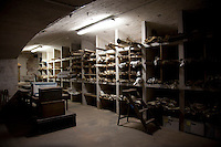 Rows of old documents are stored in floor-to-ceiling shelves in the basement
