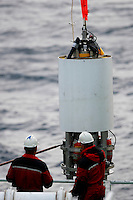 Deckhands lowering sonar unit to ship deck. The sonar buoy sits on the sea bottom and records fish species via side scan sonar in situ. Finnmark coast, Arctic Norway, North East Atlantic