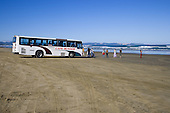 A tourist bus and tourists on Ninety Mile beach with Tauroa Peninsula in the distance. Far North. Northland, New Zealand.