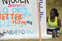NWA Democrat-Gazette/ANDY SHUPE<br /> Leondra Robinson, a freshman at the University of Arkansas from Newport, paints words Tuesday, Sept. 29, 2015, onto a block wall while participating in The Writing on the Wall Project sponsored by University Housing on the university campus in Fayetteville. Members of the campus community are encouraged to write hurtful words and names that they have experienced while on the university campus during this week. The wall will then be demolished using sledgehammers during a ceremony at 11 a.m. Friday.