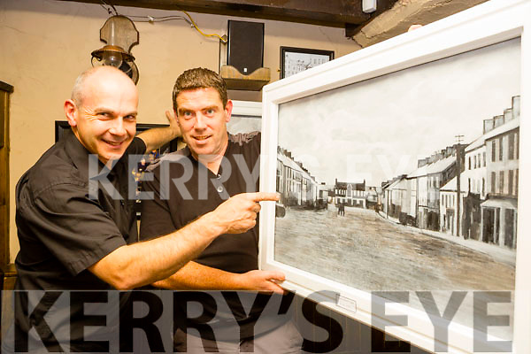 Castleisland artist Kevin Barry shows Peter Browne one of his historic paintings of Castleisland which was on exhibition in Brownes bar for the Padraig O'Keeffe festival