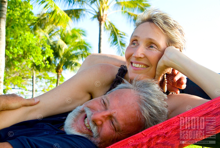 A couple relaxes in a hammock at Queens Beach, Waikiki.