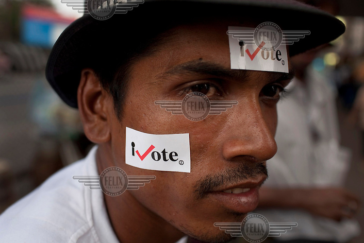 A man with stickers attached to his face that read iVote. This was part of a campaign to encourage people to vote in Burma's first elections since 1990. However, the main pro-democracy party, the NLD (National League for Democracy), boycotted the poll and other opposition groups have alleged widespread voting fraud.