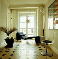 The eighteenth-century stone and marble floors of the entrance hall contrast with the futuristic Olivier Mourge chaise longue and an Arc floor lamp