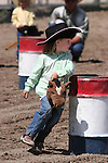 Jaylee McEwen of Fallon rounds the barrel in the Pee-Wee Stick Horse Barrel Racing event at the Fallon Junior Rodeo.  Photo by Tom Smedes.