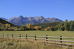 Fence, meadow and Sneffels Range with autumn colors near Telluride, Colorado.<br />
