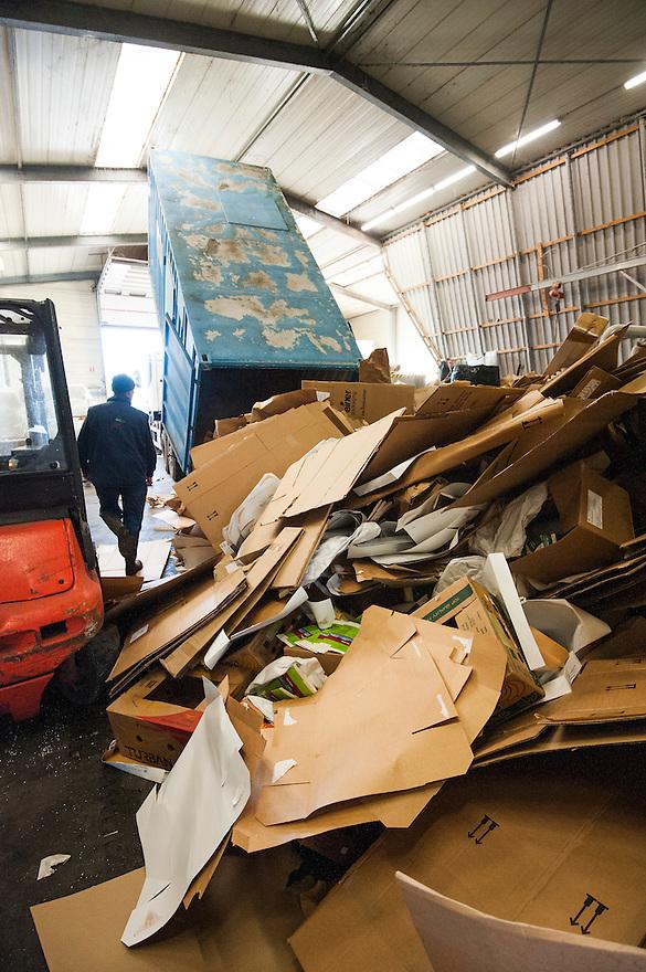 Nederland, Urk, 25 nov 2013<br /> Recyclingbedrijf de Vries. Container met karton wordt in de pershal geleegd. Hiervan worden balen geperst die aan karton of papierfabrikanten worden verkocht.<br /> Foto: Michiel Wijnbergh
