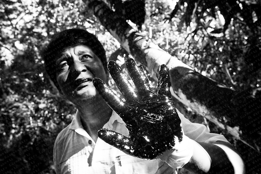 """Donald Moncayo hand is covered with crude from a open toxic pool in Ecuadorean Amazon rainforst near Lago Agrio. He is a former farmer and now a Environmentalist leads """"toxic tours,"""" seeking justice for his country and his family."""