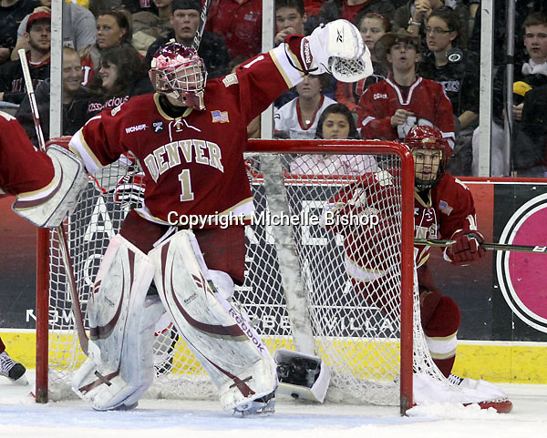 Denver goalie Sam Brittain looks to glove a floating puck during the third period. Denver beat Nebraska-Omaha 4-2 Saturday night at Qwest Center Omaha. (Photo by Michelle Bishop)