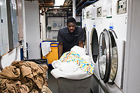Allan Baxter, 40, works in the laundry of the Harborside Inn in Edgartown, Martha's Vineyard, Massachusetts, USA. From St. Mary Parish, Jamaica, Baxter has worked at the hotel on an H2B visa for seasonal foreign workers. He spent last winter working in Stowe, Vermont, as well. The hotel has had difficulty this year getting as many H2B visas as it had in previous years. As a result, Baxter is the only person working in the laundry room on most days; it was a two-person job last year. Workers from other areas of the hotel sometimes work short shifts in the laundry room to help Baxter.