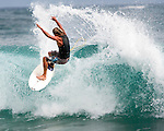 A Hawaiian surfer rides a small wave on Shipwreck Beach in Po'ipu Bay, Kaua'i, Hawaii