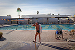 A man heads in after swimming laps and sunning at the Bell Recreation Center in Sun City, Arizona December 15, 2009. The warm climate makes outdoor recreation possible year-round.