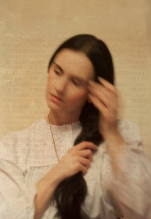 A black haired lady in a white dress with deformed face sitting in front of a wall with hands on her hair