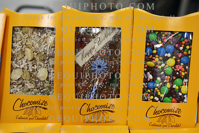 A sampling of the many custom chocolate products at Chocomize.com in Cherry Hill, New Jersey include (L) Milk Chocolate with Macadamia Nuts, Pineapple Dices and Coconut and 23 Carat Gold Flakes; (C) Milk Chocolate with a Happy Birthday greeting, Gummy Bears, Sprinkles and a Birthday Candle; (R) Dark Chocolate with Pop Rocks, Nerds and M&M's.