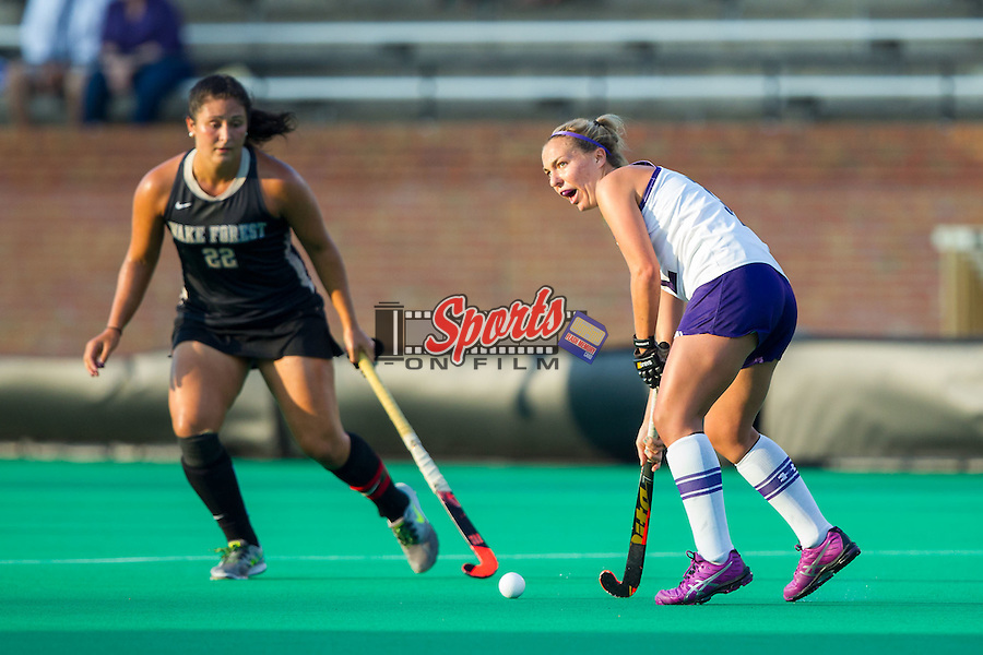 Charlotte Martin (12) of the Northwestern Wildcats looks to pass the ball away from Anna Kozniuk (22) of the Wake Forest Demon Deacons during first half action at Kentner Stadium on September 11, 2014 in Winston-Salem, North Carolina.  The Demon Deacons defeated the Wildcats 1-0.  (Brian Westerholt / Sports On Film)