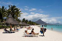 MUS, Mauritius, Black River, Flic en Flac: fliegender Haendler am Strand des Sugar Beach Resort, im Hintergrund Tamarin Mountain | MUS, Mauritius, Black River, Flic en Flac: beach at Sugar Beach Resort with Tamarin Mountain