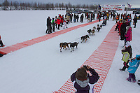 Benjamin Harper leaves the start line of the 2014 Jr. Iditarod Sled Dog Race from Happy Trails Kennel, Big Lake, Alaska<br /> Saturday February 22, 2014 <br /> <br /> Junior Iditarod Sled Dog Race 2014<br /> PHOTO BY JEFF SCHULTZ/IDITARODPHOTOS.COM  USE ONLY WITH PERMISSION