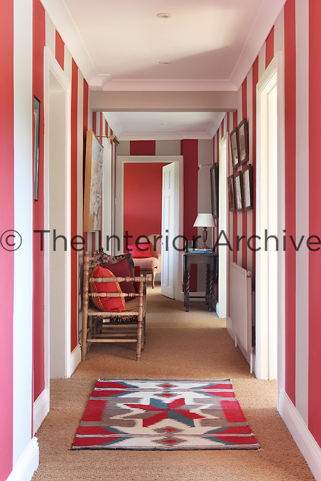 A boldly striped red and white corridor with sisal flooring