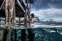 A young Bajau girl climbs up a wooden ladder into her home in the stilt village of Pulo Papan in the Togean Islands.