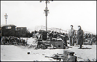 BNPS.co.uk (01202 558833)<br /> Pic: BNPS<br /> <br /> A couple stand next to wrecked trucks in Ostend.<br /> <br /> Haunting photos which capture the trail of devastation left in the wake of the Dunkirk evacuation have been unearthed after 77 years.<br /> <br /> The poignant pictures were taken soon after 330,000 Allied troops had been rescued from the beaches by an armada of little ships having been defeated by the Germans.<br /> <br /> The epic operation is about to be the subject of the new Hollywood blockbuster movie 'Dunkirk' will stars Tom Hardy and Harry Styles and is die for release on July 21.<br /> <br /> The black and white snaps show German soldiers surveying the wreckage which included destroyed ships and large military trucks lying in the surf.<br /> <br /> They are being sold by Duke's Auctioneers.