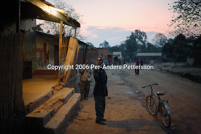 RImages MPHANDULA, MALAWI - AUGUST 18: Kaipa Rabioni Mphandula age 48, smokes a cigarette outside a local bar on August 18, 2006 in Mphandula village, about 30 miles outside Lilongwe, Malawi. He is the chief in Mphandula, a poor village in Malawi, without electricity or clean water. Nobody owns a car or a mobile phone. Most people live on farming but many still lack food. About 7000 people reside in the village and the chief estimates that there are about five-hundred orphans. Many have been affected by HIV/Aids and many of the children are orphaned. A foundation started by Madonna has decided to build an orphan center in the village through Consol Homes, a Malawi based organization. Raising Malawi is investing about 3 million dollars in the project and Madonna is scheduled to visit the village in October 2006. Malawi is a small landlocked country in Southern Africa without any natural resources. Many people are affected by the Aids epidemic. Malawi is one of the poorest countries in the world and has about 1 million orphaned children. (Photo by Per-Anders Pettersson/Exclusive by Getty Images)