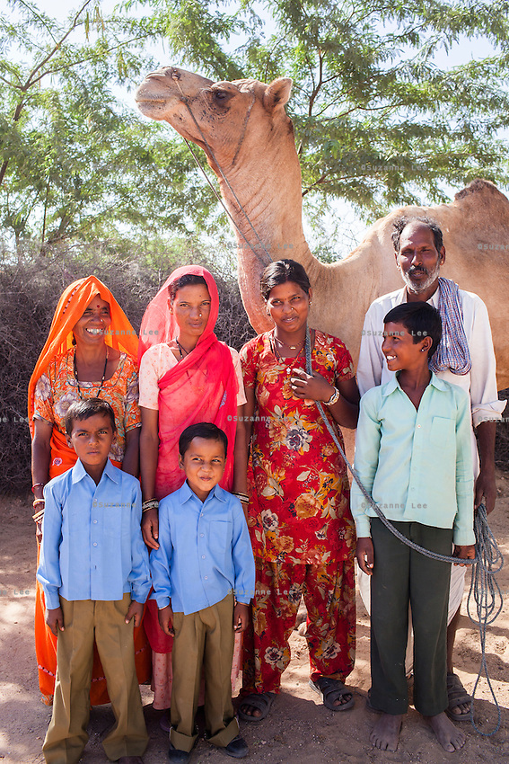 Nitu and Suki (in pink) (not their real names), stand for a portrait with their family in Jhaju village, Bikaner, Rajasthan, India on 4th October 2012. Now 18, Nitu was married off at age 10 to a boy of around the same age, but only went to live with her in-laws when she was 12, after she had finished studying up to class 6. The three sisters, aged 10, 12, and 15 were married off on the same day by their maternal grandfather while their father was hospitalized. She was abused by her young husband and in-laws so her father took her back after hearing that her husband, who works in a brick kiln, was an alcoholic and was doing drugs and crime. She had only spent a few days at her husband's house at that time. Her father (now out of the hospital) has said that she will only be allowed to return to her husband's house if he changes his ways but so far, the negotiations are still underway. Her sister, Suki, now age 20, was married off at age 12 but only went to live with her husband when she was 14. Her husband died three years after she moved in, leaving her with a daughter, now 6, and a son, now 4. She has no parents-in-laws and thus returned to her parents house after being widowed because her brother-in-law, who had become the head of the family after his brother's death, had refused to allow Suki to inherit her deceased husband's fair share of agriculture land. Although Suki's father wants her to remarry, she refuses to, hoping instead to be able to support her family through embroidery and tailoring work. The family also makes hand-loom cotton to subsidize their collective household income. Photo by Suzanne Lee for PLAN UK