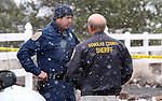 Douglas County Sheriff's Deputy Jesse McKone, left, talks with Sheriff Ron Pierini outside the home where deputies arrested 81-year-old Melvin Norlund Thursday afternoon, Nov. 21, 2013, after he allegedly shot and killed his caretaker with a shotgun in Fish Springs, near Minden, Nev. <br /> Photo by Cathleen Allison