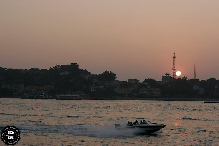 A  speedboat races though Lujiang Channel as  the sunset over Gulang Yu, in Xiamen, China.  Photograph by Douglas ZImmerman