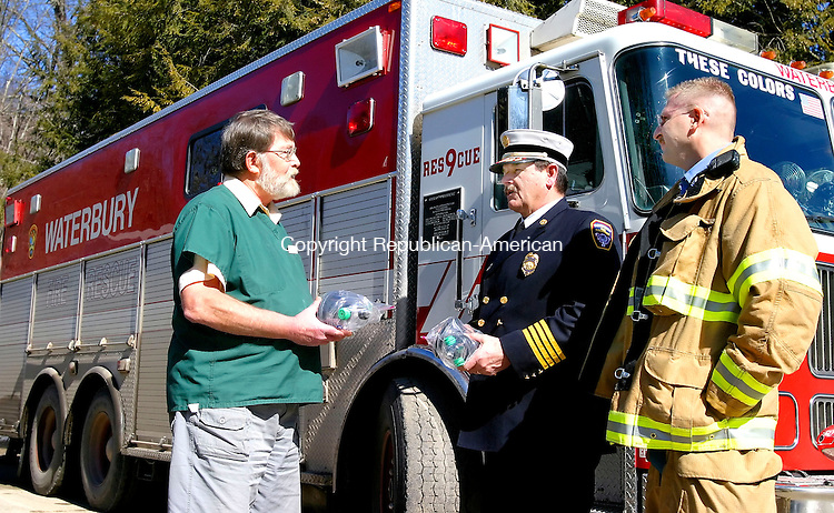 WATERBURY, CT. 28 February 2007--022807SV03--From left, Dr. Paul Kennett of the Sherman Hill Animal Hospital gives oxygen masks for pets to Asst. Chief Joe McDermott of the Waterbury Fire Dept. and Lt. Tom Meier of Rescue 9 at the hospital in Woodbury Wednesday.The masks were paid for through donations from the hospital's clients, and will be used to assist animals who are rescued from emergencies and need extra oxygen.<br /> Steven Valenti Republican-American