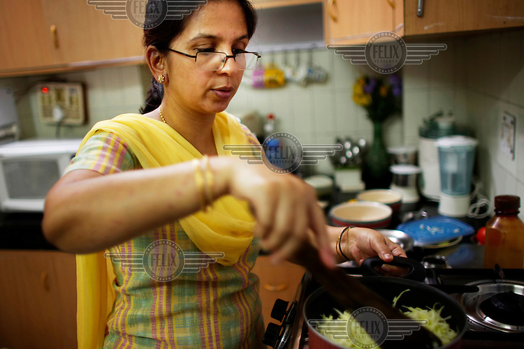 Piyali Mukherjee cooks lunch. Her family are members of India's new middle class. As new processed foods have become available to wealthy and upper middle class Indians obesity rates have soared. This family still maintains a more traditional Indian diet, having realised that newer, modern, imported foods are not necessarily better or healthier..