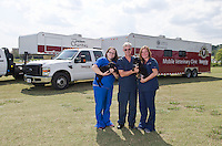 Veterinary Mobile Units with (left to right) Emily Childers, Dr. Phil Bushby and Dr. Kimberly Woodruff.
