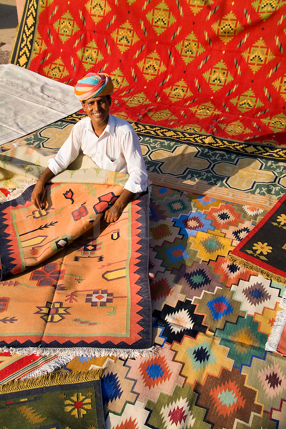 Rug designer Roopraj Prajapati shows off his hand-made carpets in village outside Jodhpur, Rajasthan, India